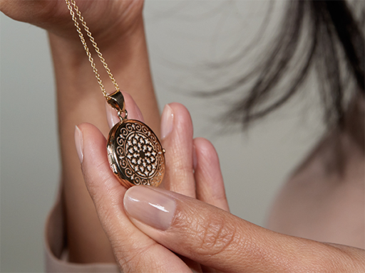 Close Up of a Woman Holding a Gold Vintage Style Round Locket