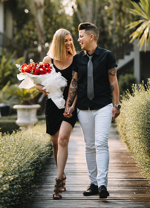 Karrie and Casey walk, holding hands, with flowers.