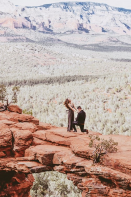 Man proposes to woman on red rock structure.