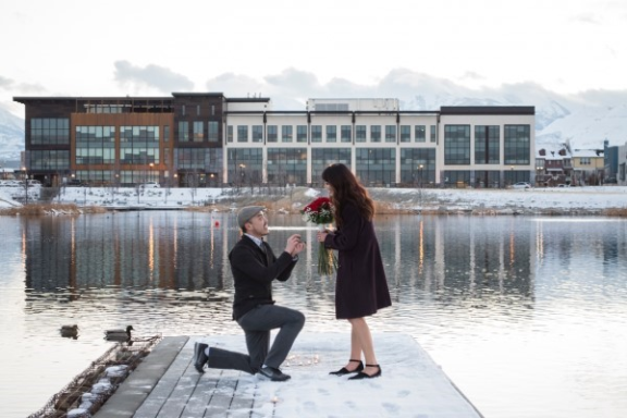 Man proposes to woman with roses on a dock.