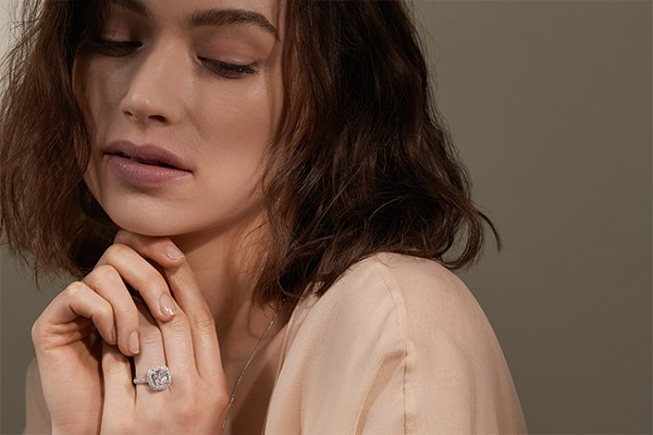 Close-up of a woman wearing a cushion shaped diamond engagement ring.