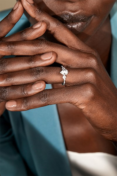 Close-up of a woman's hand wearing a pear shaped diamond engagement ring.
