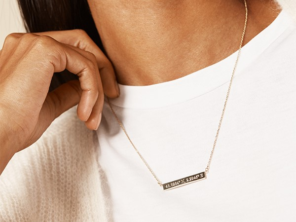 Coordinates engraved on gold bar necklace.