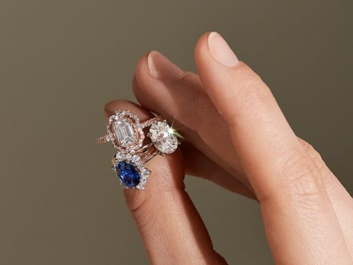 Woman holding three engagement rings.